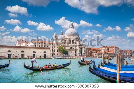Beautiful view of traditional Gondolas on famous romantic Canal Grande with historic Basilica di Santa Maria della Salute in the background on a sunny day with blue sky and clouds in Venice, Italy #390807058