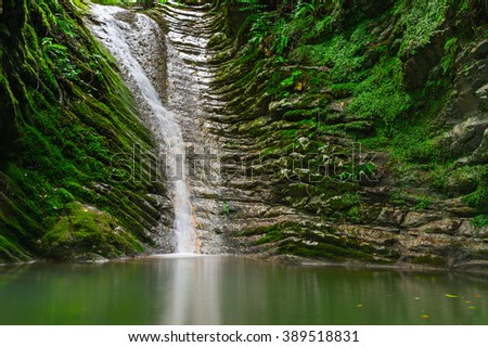 Beautiful view of waterfall landscape. Small waterfall in deep green forest scenery. Sochi, Russia nature
