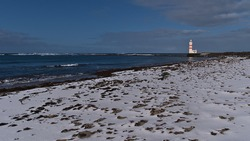Beautiful view of white and red colored old lighthouse Garður on the coast of Suðurnesjabær on Reykjanes peninsula, Iceland with snow-covered beach in winter season on sunny day.