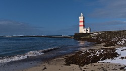 Beautiful view of white and red colored old lighthouse Garður on the coast of Suðurnesjabær on Reykjanes peninsula, Iceland with beach and snow in winter season on sunny day.