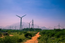 Beautiful view of Windmills or Wind Turbines farm in Nagercoil, South India. With a colorful sky and mountains as a background.