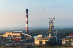 Beautiful view on coal mining 'Boze Dary' in Katowice, Silesia, Poland seen from mining heap at sunrise. Nature versus industry. A mine surrounded by forests. Mining infrastructure.