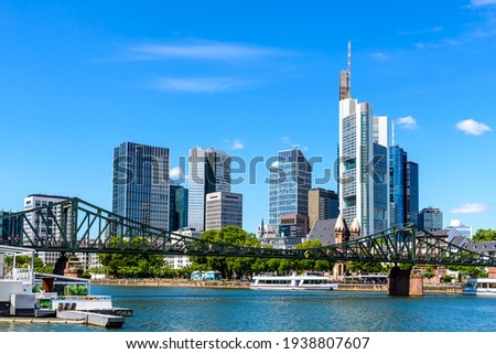 Beautiful view on  Frankfurt am Main skyline cityscape with blue sky, clouds, Main river, bridge Eiserner Steg in spring. Hessen, Hesse, Germany