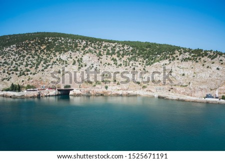 Beautiful view on sea. Rock and sea. Summer time. Sunny day. Vacation. Beautiful view of the sea. Rock and sea. Summertime. Sunny day. Bluewater. No people. Stock Photo. Nature. Clean sky. Mountains.