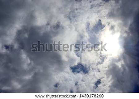 Beautiful view onto sunbeams with some lens flares and clouds on a blue sky #1430178260