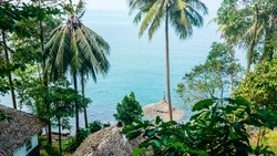 Beautiful View over Bamboo Huts in colorful green Rainforest with Palmtrees and the blue Ocean Water at the Horizon