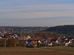 Beautiful view over residential area in Hessigheim, Germany with mainly single- and two-family houses and vineyards in front as well as village Mudelsheim in background in autumn season.