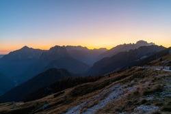 beautiful view over the Julian Alps with the sun setting over a beautiful mountain ridge on a cloudless day in autumn. Enjoying beautiful mountain vistas during twilight while traveling in Europe.