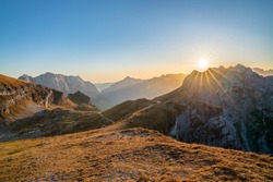 beautiful view over the Julian Alps with the sun setting over a beautiful mountain ridge on a sunny day in autumn. Enjoying beautiful mountain vistas with a sun star while traveling in Europe.