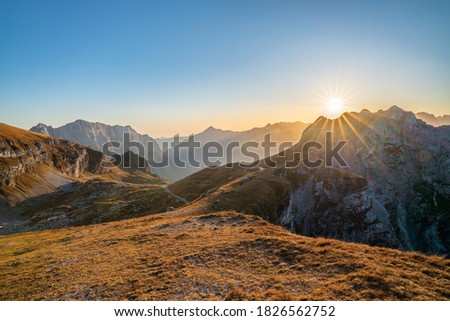 beautiful view over the Julian Alps with the sun setting over a beautiful mountain ridge on a sunny day in autumn. Enjoying beautiful mountain vistas with a sun star while traveling in Europe.  Foto stock ©