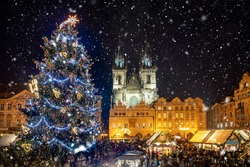 Beautiful view to the old town square of Prague during night time with a Christmas market in winter time with snow falling, Czech Republic
