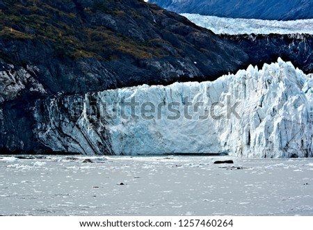 Beautiful view water bordered by the face of a glacier illuminated by the ray of sunshine surrounded by the slopes of the mountains creating a wonderful outdoor experience with a natural backdrop #1257460264