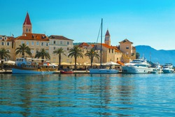 Beautiful view with luxury yachts and boats in the touristic harbor. Popular waterfront promenade with palms and street cafes, Trogir, Dalmatia, Croatia, Europe