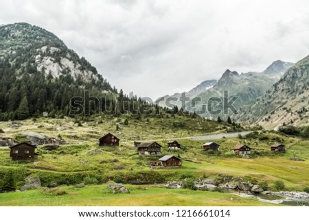 Beautiful views over Swiss landscape with old hauses, meadows and mountains; natural environment in valley of Swiss Alps