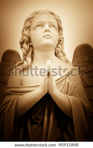 Beautiful vintage image of a praying angel in sepia shades with light illuminating his face