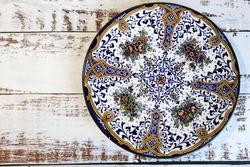 Beautiful vintage ornamental plate on wooden table