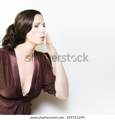 Beautiful vintage woman whispering confidentially behind her raised hand as she shares her secrets in a Secret Whispers concept