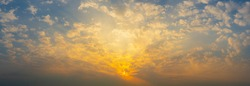 Beautiful Vivid sky painted by the sun leaving bright golden shades.Dense clouds in twilight sky in winter evening.Image of cloud sky on evening time.Evening Vivid  sky with clouds.