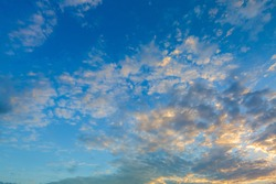 Beautiful Vivid sky painted by the sun leaving bright golden shades.Dense clouds in twilight sky in winter evening.Image of cloud sky on evening time.Evening Vivid sky with clouds