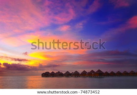 Beautiful vivid sunset over water villas in the Indian ocean, Maldives - stock photo