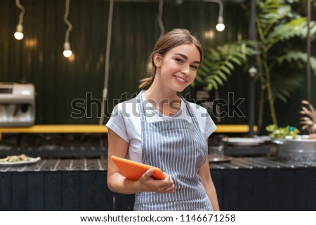 Beautiful waitress. Beautiful waitress wearing her uniform feeling good while welcoming guests of restaurant #1146671258