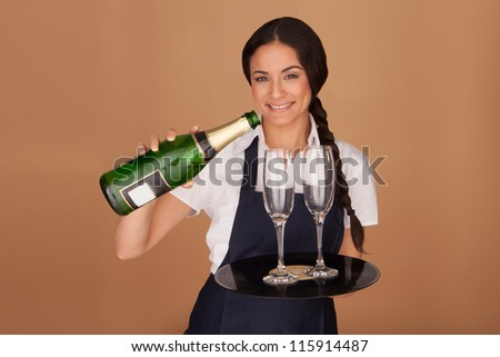 Beautiful waitress pouring champagne into two elegant flutes that she is balancing on a tray