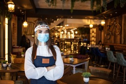 Beautiful waitress working at a restaurant wearing a facemask and visor. Happy female waitress with visor and protective face mask at restaurant during coronavirus epidemic.