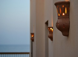 Beautiful wall lamps in the evening. Lights are just turned on. Outdoor lighting is also decorative