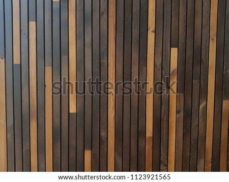 Beautiful wall with thin lacquered wooden dark brown and light brown boards #1123921565
