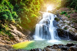 Beautiful waterfall at the mountain with blue sky and white cumulus clouds. Waterfall in tropical green tree forest. Waterfall is flowing in jungle. Nature abstract background. Granite rock mountain.