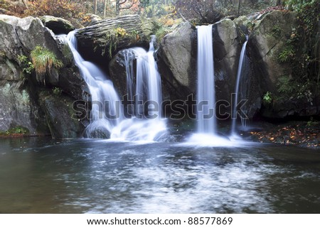 beautiful waterfall flowing into a pool during in autumn
