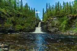 Beautiful waterfall flushing down eroded rocks of slate stone, surrounded by green trees and a blue sky