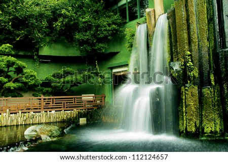 Beautiful waterfall in Chinese Classical Garden called Nan Lian in Hong Kong situated on the Kowloon Island. Blurred motion.