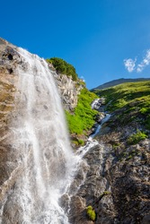 beautiful waterfall in European mountains with a blue sky above