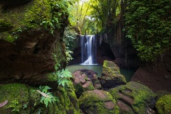 Beautiful waterfall in rainforest. Tropical landscape. Slow shutter speed, motion photography. Foreground with big stones. Nature concept. Travel and adventure. Suwat waterfall, Bali, Indonesia