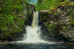 Beautiful waterfall in the Swedish highlands with water flushing down an eroded slate rock wall with green vegetation growing on the sides