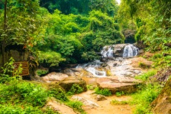 Beautiful waterfall Mae Sa, Thailand. Fresh and pure water stream is flowing on the rock stone ground in tropical rainforest. Fresh plants and trees above river. Vibrant colors in pure nature.