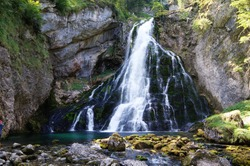 beautiful waterfall of a mountain stream with wet mossy stones in the foreground and a relatively long shutter speed,