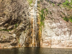 Beautiful waterfall rolling across the stone wall in the mountains of Minas Gerais state, Brazil. The name of this waterfall is Cachoeira Rabo de Cavalo