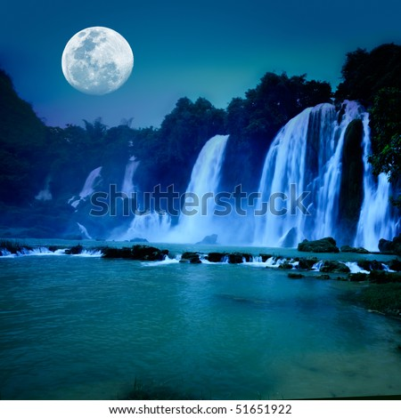 Beautiful waterfall under moonlight at night time