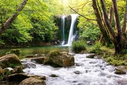 Beautiful waterfall with a river and a pond in a magical and idyllic scenery. Gorg de Santa Margarida, Planes d'Hostoles, Olot, Garrotxa, Girona, Catalonia, Spain.