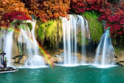 Beautiful waterfall with rainbow in autumn forest