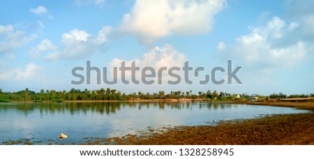Beautiful Waterscape With Green Trees and Cloudy Blue Sky Background at Tamil Nadu in India