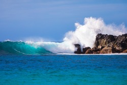 Beautiful waves crashing on rocks in Waimea Bay in the island of Oahu, Hawaii, USA.