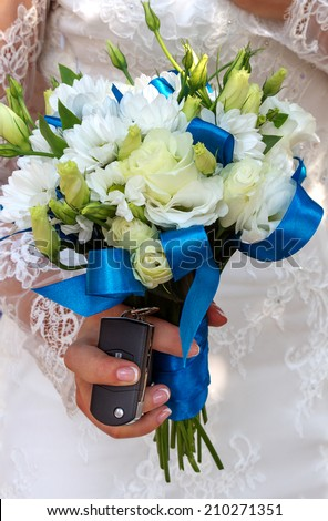 Beautiful wedding bouquet in hands of the bride and wedding gift keychain alarm on a new car