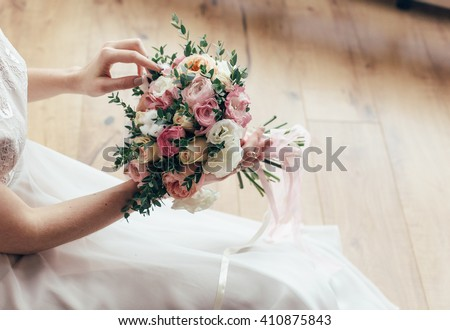 Beautiful wedding bouquet in hands of the bride. Peony rose, cotton, roses. Pink and Peach. Trendy and modern wedding flowers. Ideal photo for commercial.