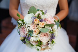 Beautiful wedding bouquet in hands of the bride. Rose, cotton, roses. Pink, white and Peach. Trendy and modern wedding flowers. Soft pastels.