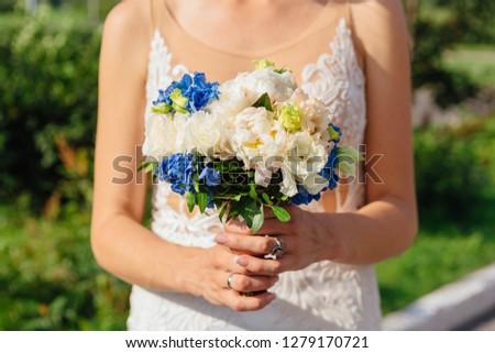 Beautiful wedding bouquet in the bride's hands #1279170721