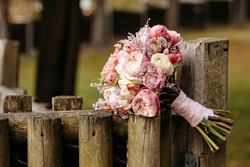 Beautiful wedding bouquet lying on old wooden fence over blur background. Flowers decoration for celebration. Concept of freshness and nature