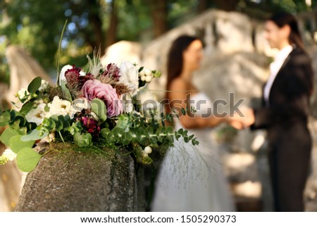 Beautiful wedding bouquet on railing against blurred lesbian couple outdoors outdoors